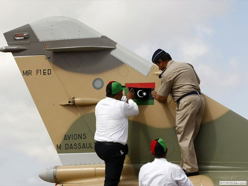 Libyan Air Force Brigadier General Mohammed Rajab (R) replaces the all-green Gaddafi-era Libyan flag on the tail of a Libyan Air Force Mirage F1 fighter jet with a Kingdom of Libya flag  (2)